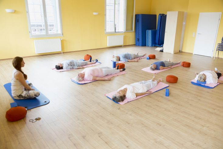 Yoga class with senior women lying down on exercise mat, relaxation exercise